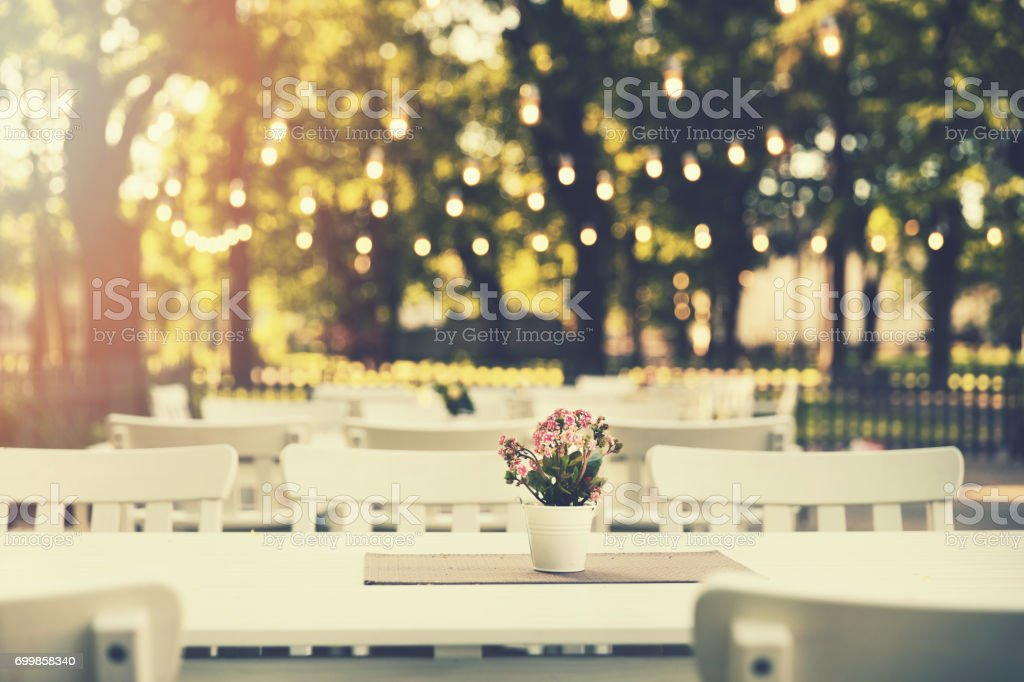 romantic outdoor restaurant in park with string lights at sunset stock photo