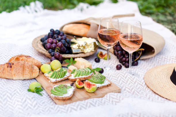 Romantic picnic with two wineglasses, delicious food, healthy fruits: avocado, grapes, figs. Straw hat, bag, sandwiches, croissants, cheese are on white plaid. Lunch in italian or french style stock photo