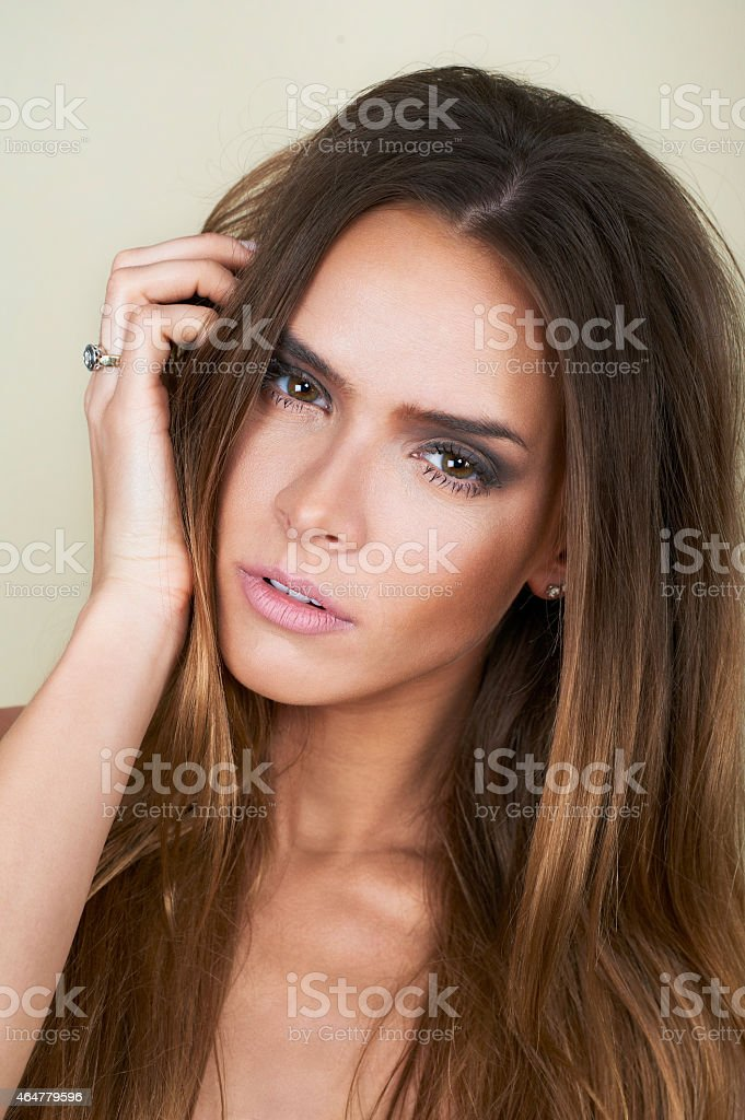 Romantic picture of a beautiful young woman with dark hair Beautiful female model touching her face on brown background 2015 Stock Photo
