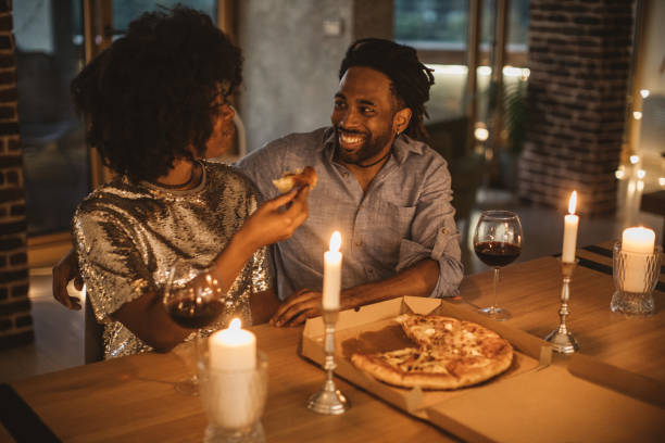 Romantic pizza evening at home Young couple having romantic dinner at home. Eating pizza and drinking wine. Well dressed. date night romance stock pictures, royalty-free photos & images
