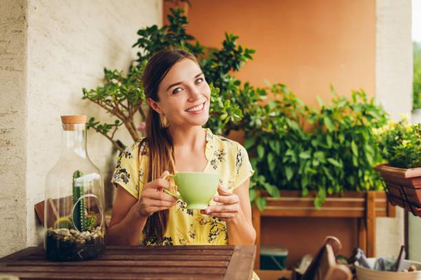 Romantisches Porträt von schönen jungen Frau trägt gelbes Kleid, entspannend auf dem Balkon zwischen vielen grünen Pflanzen, halten Tasse Tee oder Kaffee – Foto