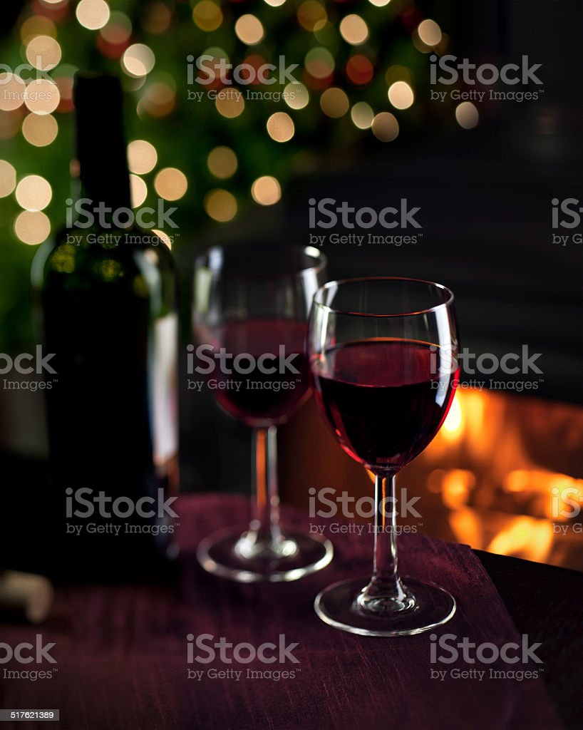 Romantic Red Wine by a Fireplace at Christmas stock photo