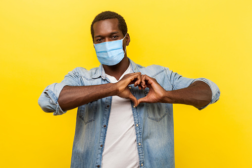 Romantic relations. Portrait of handsome cheerful man with surgical medical mask making heart shape with hands, expressing love feelings or friendship.