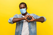 Romantic relations. Portrait of handsome cheerful man with surgical medical mask making heart shape with hands, expressing love feelings or friendship. indoor studio shot isolated on yellow background