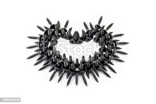 istock Romantic relationship from the point of view of men. Black heart with thorns laid out whit black screws on white background 696584658