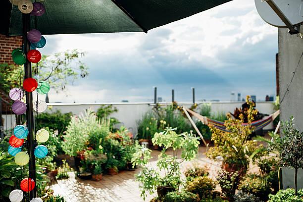 romantische dachterrasse in berlin, hängematte im hintergrund - dachgarten stock-fotos und bilder