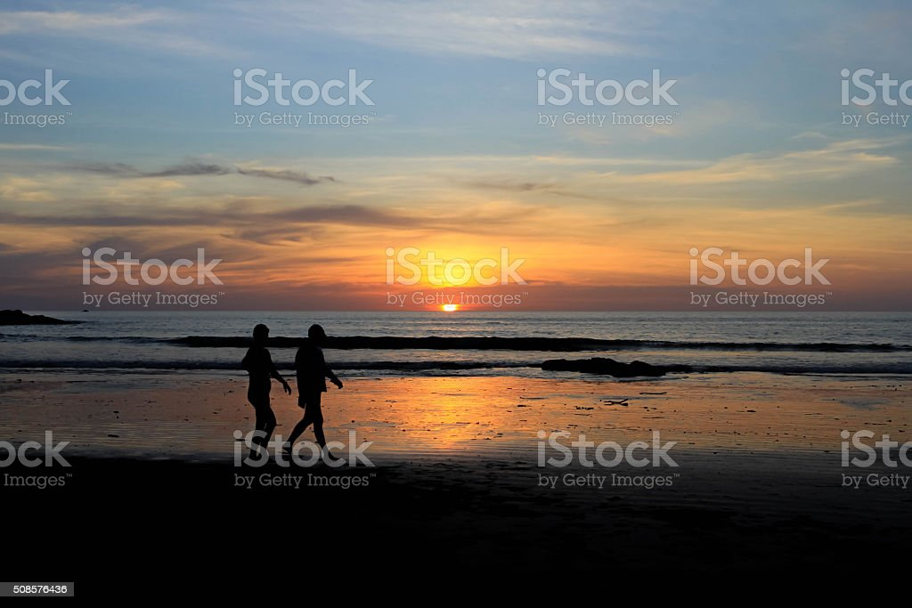 Romantic scene of a couple silhouette and sunset background stock photo