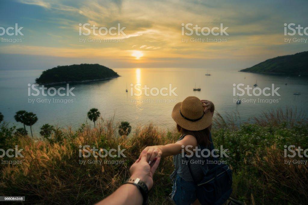 Romantisk scen av ung kärlek par håller hand beskådar peka ser solnedgången vid Promthep Cape Phuket, Thailand. - Royaltyfri Blå Bildbanksbilder