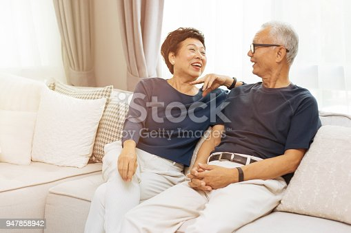 istock Romantic senior Asian couple laughing and sitting on sofa at home 947858942