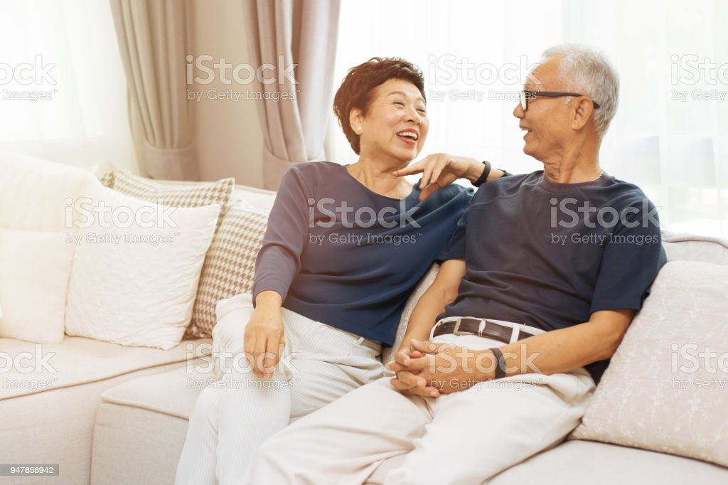 Romantic senior Asian couple laughing and sitting on sofa at home stock photo