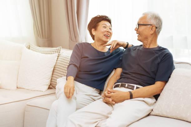 Romantisches senior asiatischen paar zu lachen und zu Hause auf Sofa sitzen – Foto