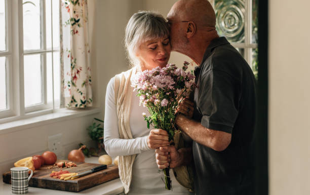 romantic senior couple at home expressing their love - senior valentine stock photos and pictures