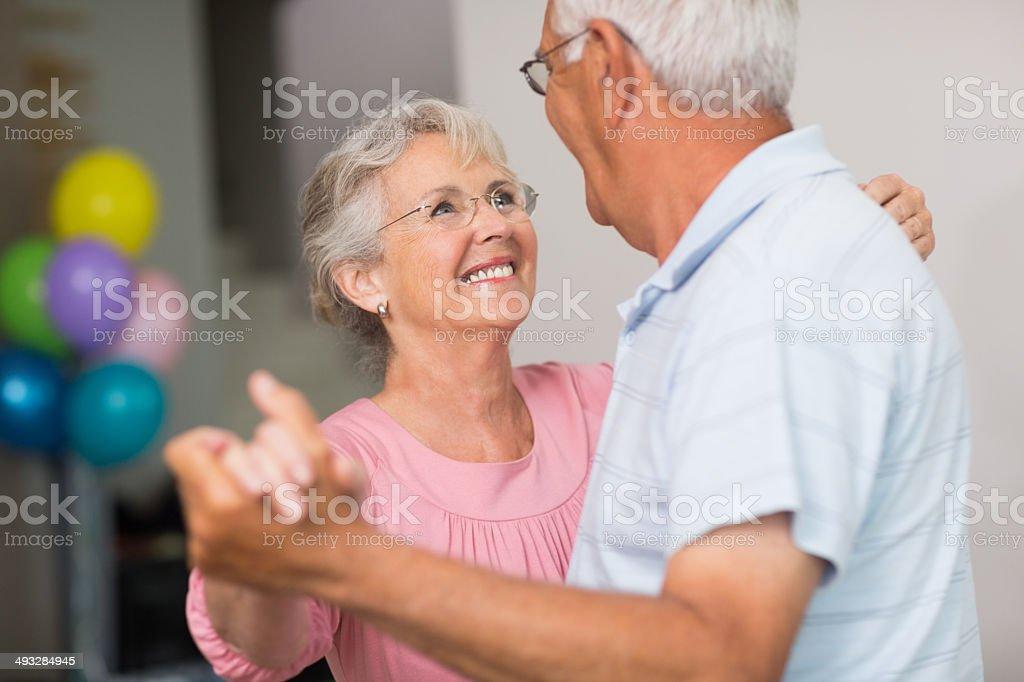 Romantic senior couple dancing at home stock photo