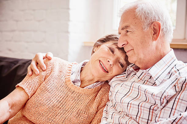 Romantic senior couple reminiscing on sofa stock photo