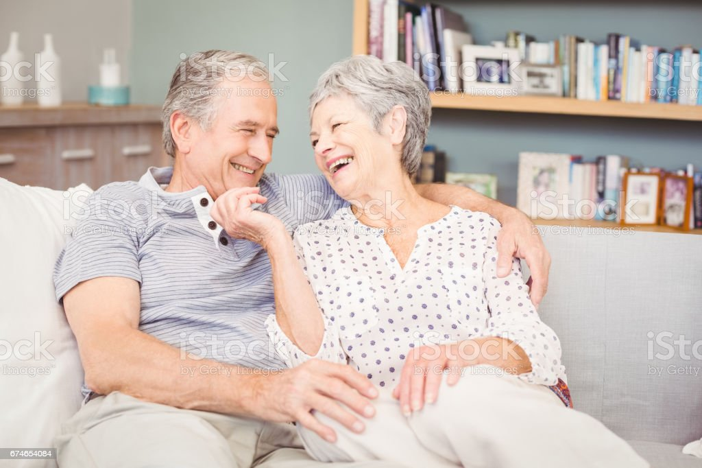 Romantic senior couple sitting on sofa in living room at home