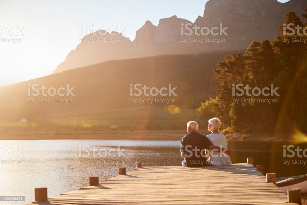 Romantic Senior Couple Sitting On Wooden Jetty By Lake stock photo