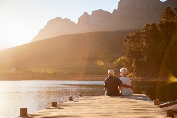 romantic senior couple sitting on wooden jetty by lake - idosos imagens e fotografias de stock