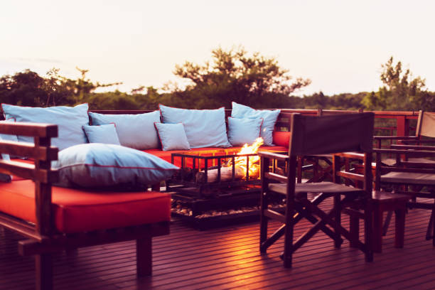 Romantic Setting on a Wooden Deck with Fireplace and Outdoor Furniture at a Holiday Resort in Africa stock photo