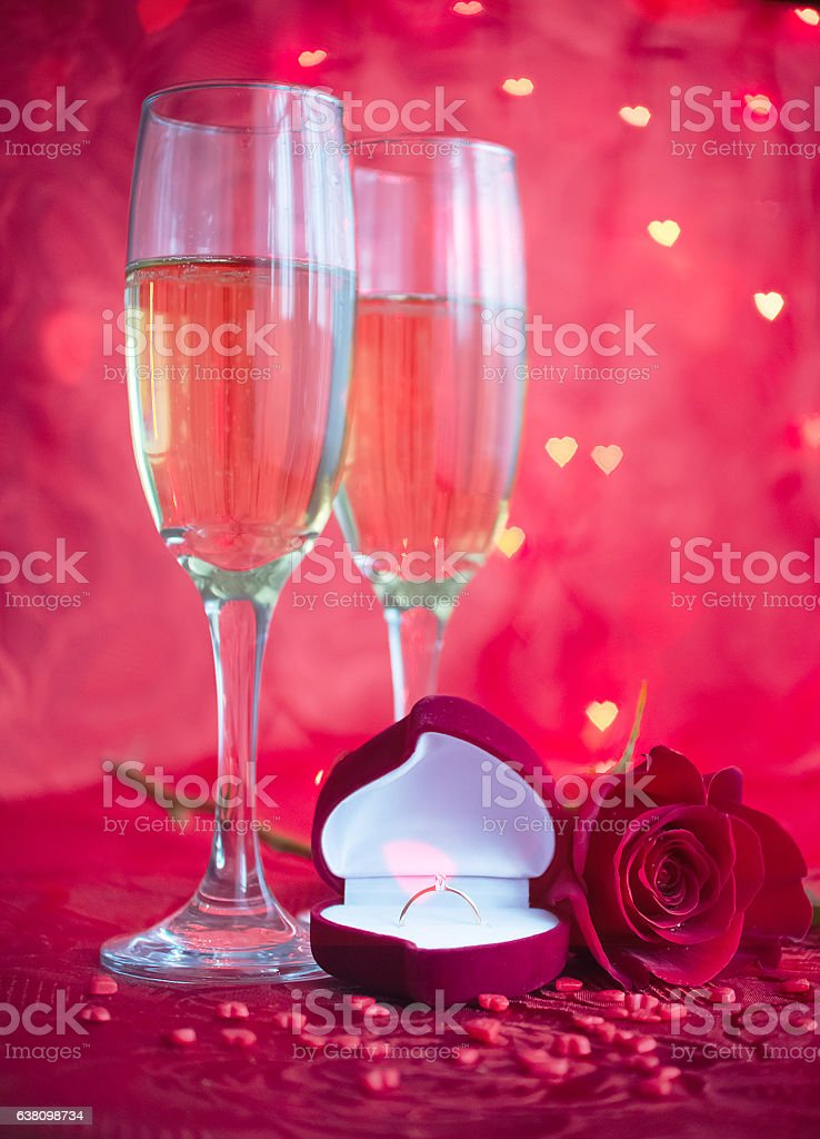 Romantic setup with champagne, rose and engagement ring stock photo