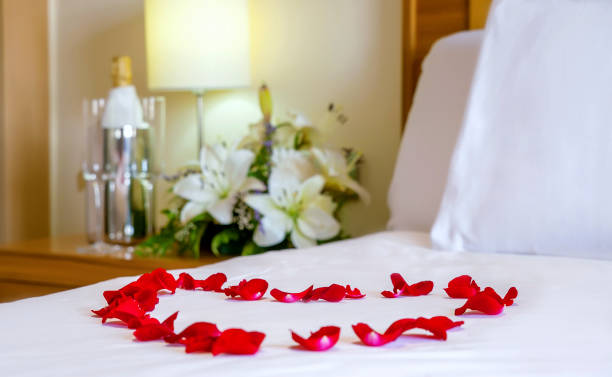 Romantic setup with honeymoon bed with focus on the heart-shaped rose petals Horizontal perspective of a romantic setup with honeymoon bed with focus on the heart-shaped rose petals. White bedding, flowers, champagne flutes, concept for romance, honeymoon, or Valentine Day. luxury hotel room stock pictures, royalty-free photos & images