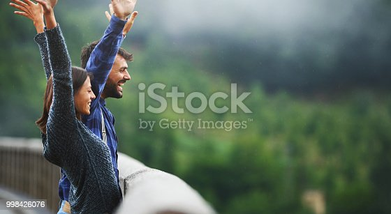 Closeup side view of a young couple standing on a bridge over a canyon and shouting at the distance. Copy space