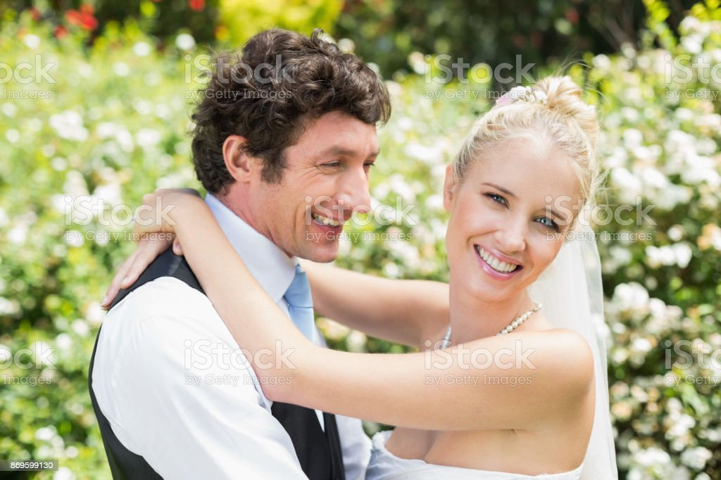 Romantic smiling newlywed couple hugging each other stock photo