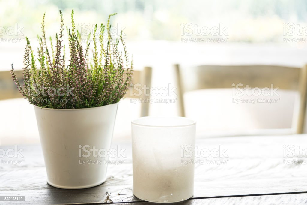 romantic soft scene of purple heather, flower pot, chair, candle, wooden table-1 stock photo