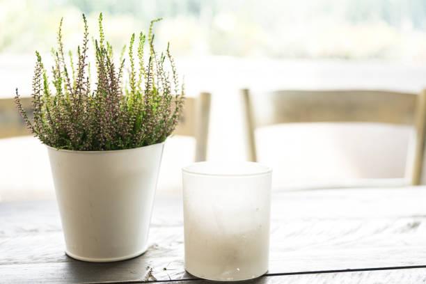 romantische weichen szene lila heidekraut, blumentopf, stuhl, kerze, hölzerne tabelle-1 - küche deko lila stock-fotos und bilder