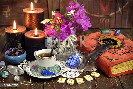 811119304 istock photo Romantic still life with cup of tea, witch book, runes and black candles. 1249942553