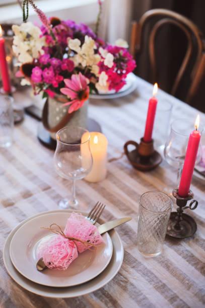 romantischen sommer abendessen im gemütlichen landhaus. festliche tischdekoration mit blumen und kerzen in lila tönen - geheime garten parties stock-fotos und bilder