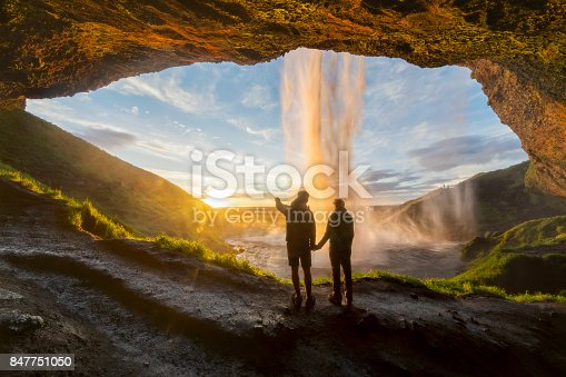 Couple under the waterfall, man pointing with finger to the sun