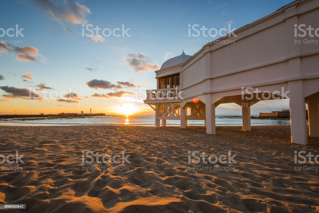Romantic sunset at Cadiz beach with famous pier stock photo