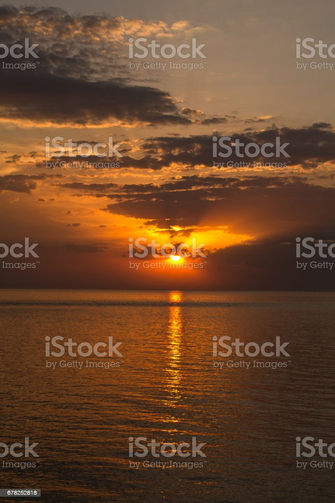 Romantic sunset at the beach. Direct view to the horizont with water and clouds. Colorful athmosphere. stock photo