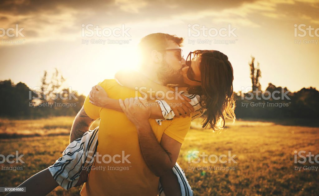 Romantic sunset. Closeup of late 20's couple enjoying each other's company on a beautiful summer sunset. They are kissing, laughing and being carefree. 20-29 Years Stock Photo