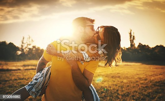 Closeup of late 20's couple enjoying each other's company on a beautiful summer sunset. They are kissing, laughing and being carefree.