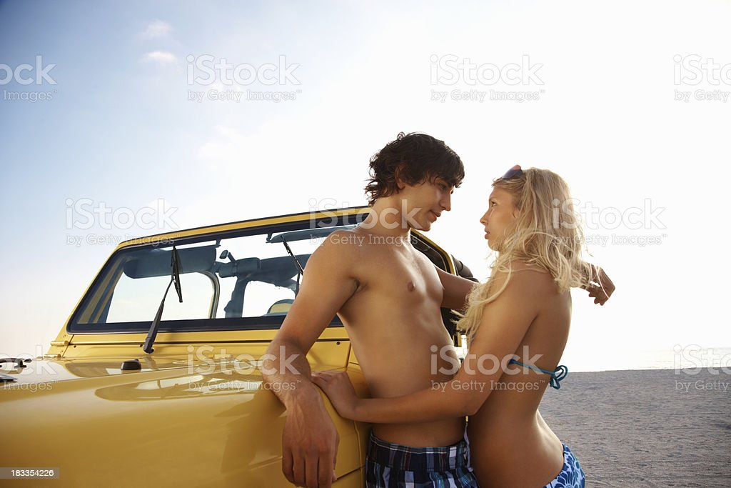 Romantic teenage couple leaning against jeep on the beach royalty-free stock photo