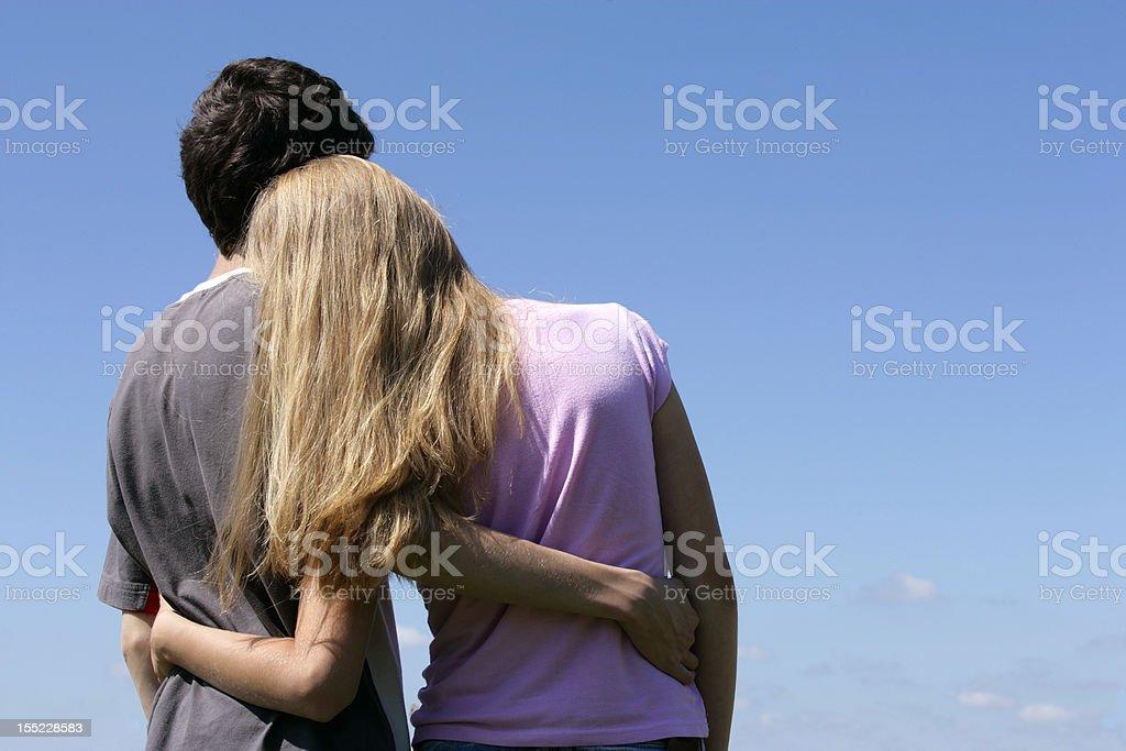 Romantic teenage couple looking at blue sky hugging stock photo