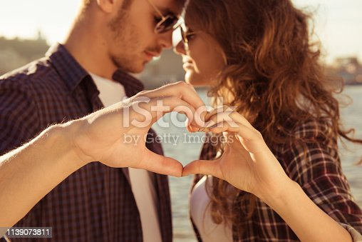 950598260 istock photo Romantic tender couple in love gesturing a heart with fingers near river 1139073811