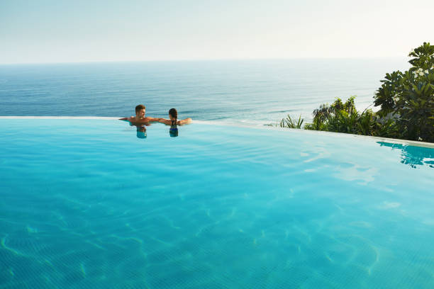Romantic Vacation For Couple In Love. People In Summer Pool Romantic Vacation For Couple In Love. Happy People Relaxing In Infinity Edge Swimming Pool Water, Enjoying Beautiful Sea View. Man, Woman Together On Summer Travel To Luxury Resort. Summertime Relax infinity pool stock pictures, royalty-free photos & images