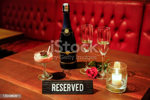 Close up shot of a reserved romantic table setting for two lovers with a champagne bottle and champagne flute above table, with candle light setting and a rose flower decoration