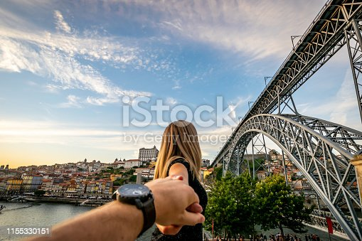 A woman tends back her hand into the hand of her husband. In the background, blue skies and soft white clouds roam over the Douro river between the cities of Porto and Vila Nova de Gaia displaying it's colourful City-line. The double decked metal arched bridge, Don Luís I bridge, is displayed to the right.