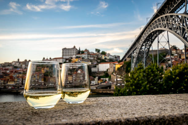 Romantic view of Porto and the Douro river through wine glasses. In the background of two white wine glasses are Blue skies and soft white clouds roaming over the Douro river between the cities of Porto and Vila Nova de Gaia displaying it's colourful City-line. The double decked metal arched bridge, Don Luís I bridge, is displayed to the right. duero stock pictures, royalty-free photos & images