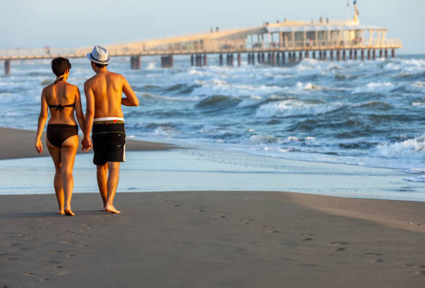 Romantic walk of a couple in love on the beach i