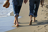 Unrecognizable family lying at the beach with sandy feet. Focus is on feet.