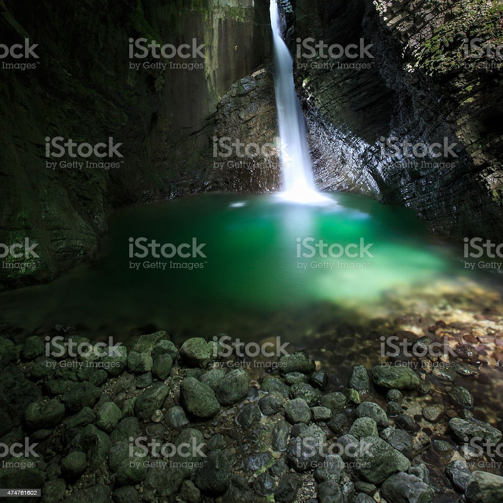Romantic waterfall flowing through a crevasse to green lake stock photo