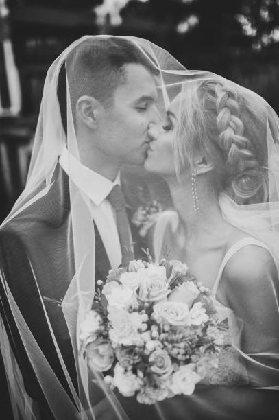 romantic wedding moment, couple of newlyweds kissing under the veil in nature in the park. black and white photo. - foto di matrimonio foto e immagini stock