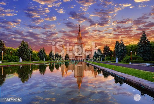 Panoramic view of sunset campus of Moscow university  under dramatic sky with water reflections and swimming red ducks