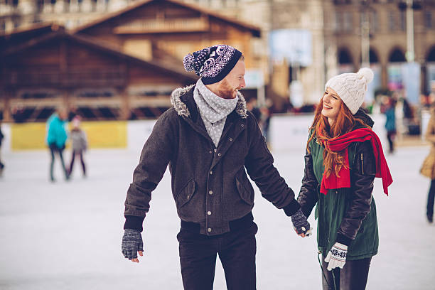 Romantic winter vacation Romantic coupleholding hands on the ice rink in the winter. The couple is wearing casual winter coats and ice skates, standing on the ice together. ice skating stock pictures, royalty-free photos & images