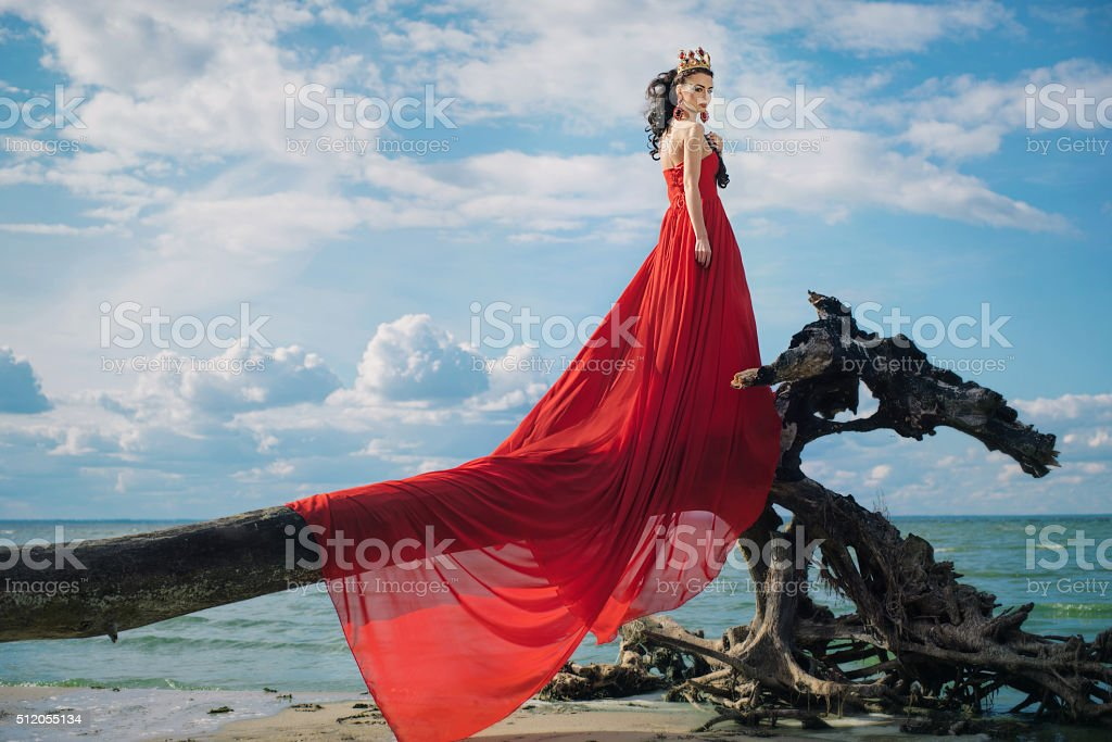 Romantic woman in fluttering red dress stock photo
