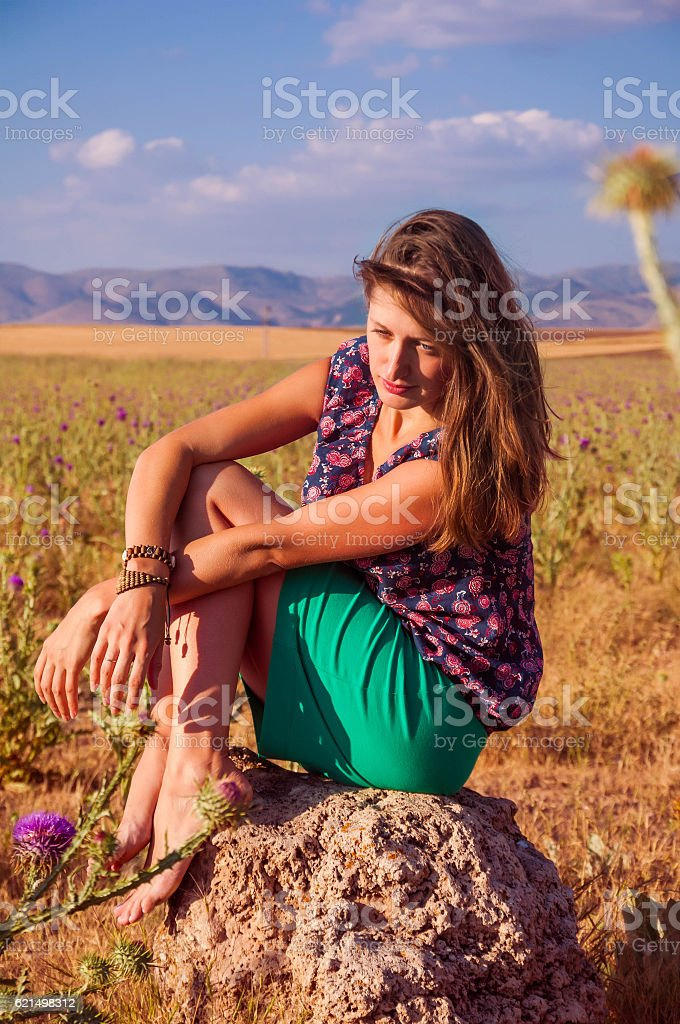 Romantic woman sitting in the field, autumn season Lizenzfreies stock-foto